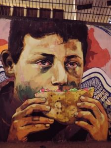 [The wall of Mohammed Mahmoud Street, a few meters from the entrance of the gate of the American University in Cairo. A poor child, (most probably a street child) eating a falafel sandwich. Captured 25 November 2013]