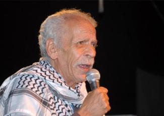 Figure 1: Photo of Ahmed Fouad Nigm wearing a Palestinian keffiyeh, accompanying Sinan Antoon's translation of Nigm's poem خطي الخط دا (This Script Is My Script).